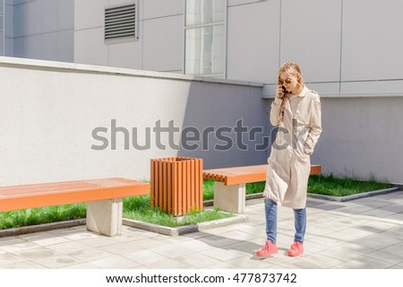 young beautiful girl with long hair fanned by the wind, wearing a raincoat, talking on cell phone on the street. telephone communication, liaison, pleasant conversation about the business #477873742