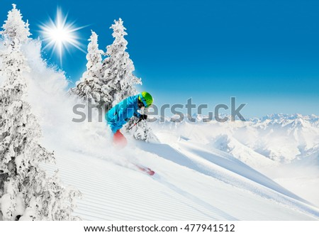 Skier on piste running downhill in beautiful Alpine landscape. Blue sky on background. Free space for text #477941512