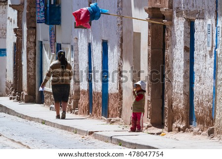 Maras Peru -May 18 : Young boy standing outside of his door eating fresh fruit with a traditional plastic flag indicating the Chicha is ready. May 18 2016, Maras Peru. #478047754