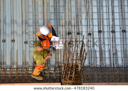 Aerial view of unrecognized civil engineers inspecting the work progress in a construction site. Building development concept with copy space #478183240