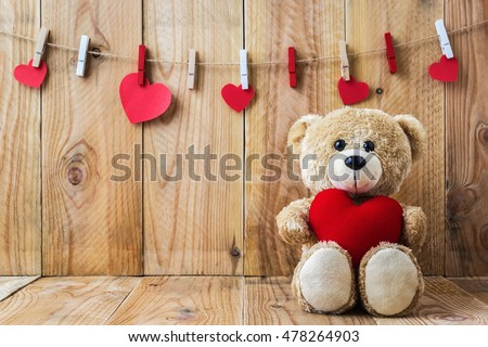 A photo of Teddy bear holding a heart-shaped pillow on plank wood board with wood board background