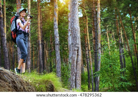 Adventure concept. Happy young woman hiking in the forest. Active lifestyle, tourism. Tourist equipment. #478295362