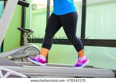 Jogging to lose weight to be healthy,legs wearing sneakers running on treadmill. #478343170