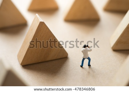 Miniature man taking photo with triangle wood block, traveling concept.