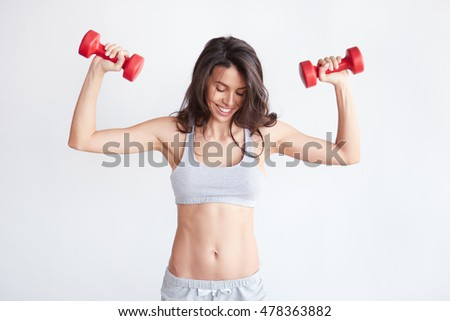 Athletic woman with dumbbells isolated on white background. Happy trained female smiling looking at her abs #478363882