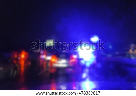 lighting of police car at night during accident on the road when raining.  -blurred picture.
