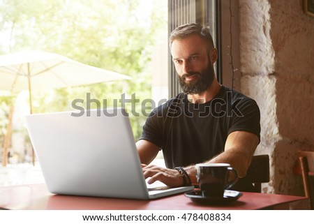 Handsome Bearded Businessman Wearing Black Tshirt Working Laptop Wood Table Urban Cafe.Young Manager Work Notebook Modern Interior Design Place.Coworking Process Business Startup.Blurred Background #478408834