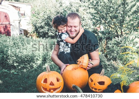 Halloween. Daughter hugging father. Man cuts a lid from a pumpkin as he prepares a jack-o-lantern. Decoration for party. Toned photo. Family.