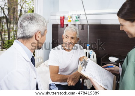 Patient Looking At Doctor While Nurse Holding Reports #478415389