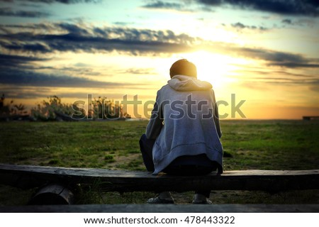 Lonely Man sit on the Bench at Sunset Background Royalty-Free Stock Photo #478443322