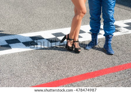 Woman sexy legs and driver in blue racing suit on motorsport checkered asphalt line #478474987