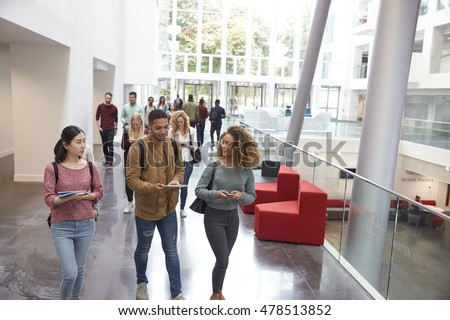 Students walk and talk using mobile devices in university Royalty-Free Stock Photo #478513852