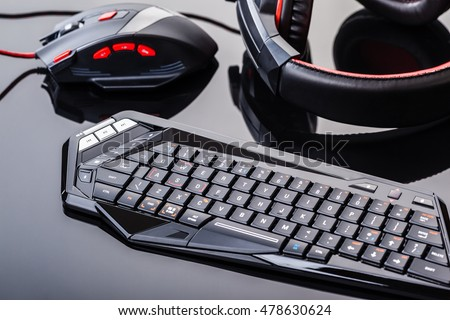 a gaming keyboard, mouse and headset shot over a dark reflective surface Royalty-Free Stock Photo #478630624