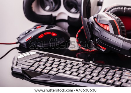 a gaming keyboard, mouse, headset and Virtual reality glasses shot over a dark reflective surface Royalty-Free Stock Photo #478630630