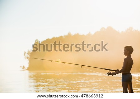 Fisherman boy stands in the water #478663912