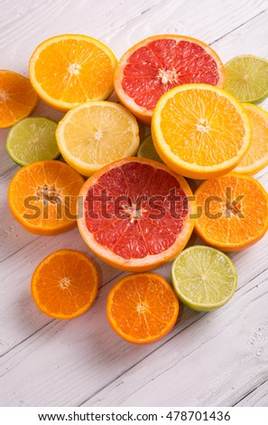 Cut citrus fruits on a background of white boards. #478701436
