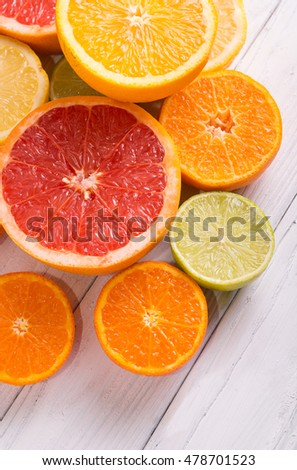 Cut citrus fruits on a background of white boards. #478701523