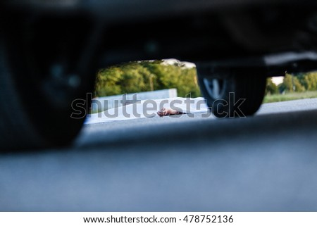 Dead body with hand sticking out from under white sheet with automobile in front of it Royalty-Free Stock Photo #478752136