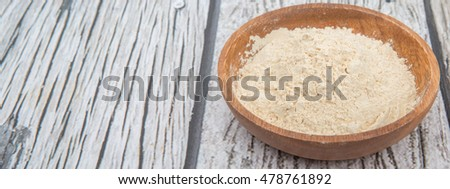 Super food maca powder in wooden bowl over wooden background #478761892