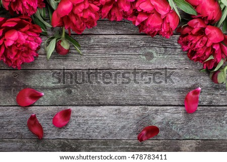 Floral frame with pink peonies flowers on rustic wooden background. Selective focus, place for text, top view #478783411