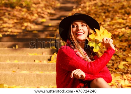 Woman relaxing in autumn fall park. Young feshionable female stylish black hat holding yellow maple leaves in hand, enjoying sunlight #478924240