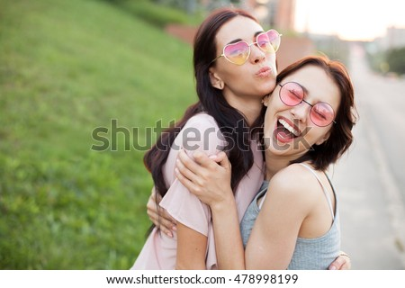 Two cheerful young women walking on the street and hugging at sunset. Best friends