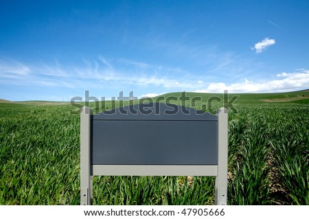 Blank wooden sign Against green field and blue sky