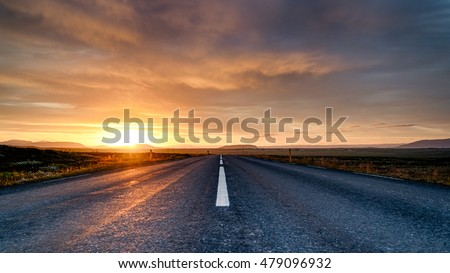Clouds over an empty road lit magnificently by rising sun #479096932