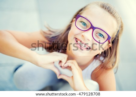Smiling little girl with braces and glasses showing heart with hands. #479128708