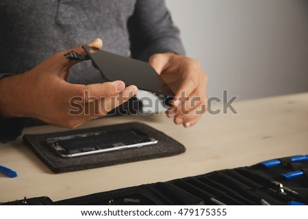 Master holds new screen for replacement above disassembled smartphone in his laboratory, tool kit with instruments in front of him on white table, space for your text on right #479175355
