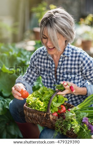 a summer day, a middle aged woman is sitting with her basket of vegetables in her garden,she's happy and proud of her harvest, she has one vegetable in one's hand #479329390