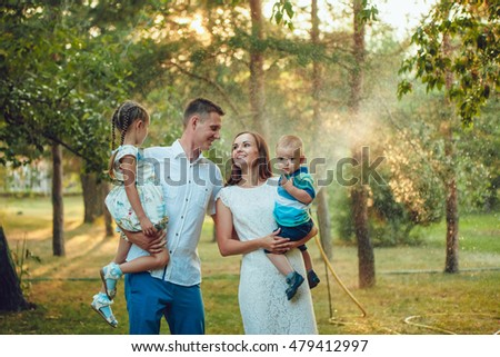 Happy young family of four people walking and having fun in the park #479412997