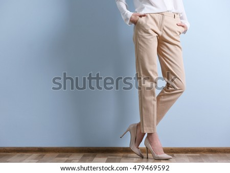 Beautiful young woman in a white shirt and beige pants on blue wall background #479469592