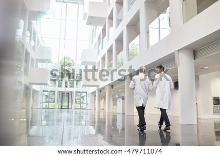 Rear View Of Doctors Talking As They Walk Through Hospital Royalty-Free Stock Photo #479711074