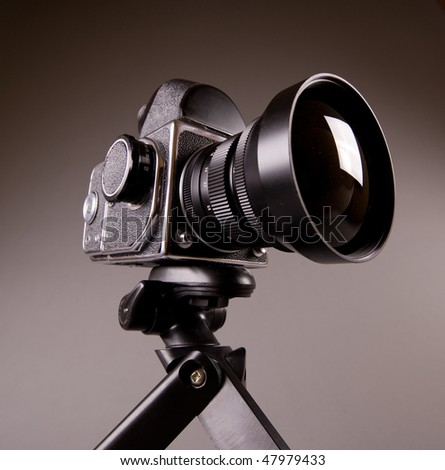 Old middle format photo camera with tripod on grey in Hi-Res