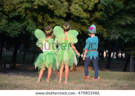 Boy dressed as Peter Pan and two girls in fairy costume