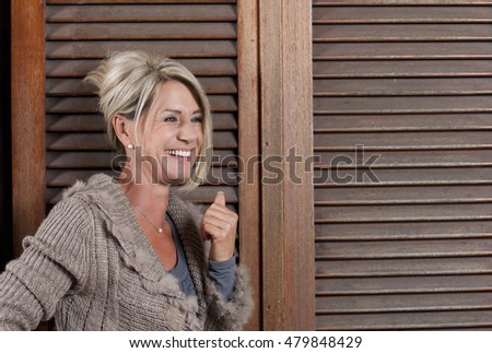 Happy smiling matured woman in front of a wooden Wall #479848429