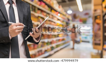 Businessman using the tablet and writing the order stock on Supermarket blur background, business technology concept #479994979