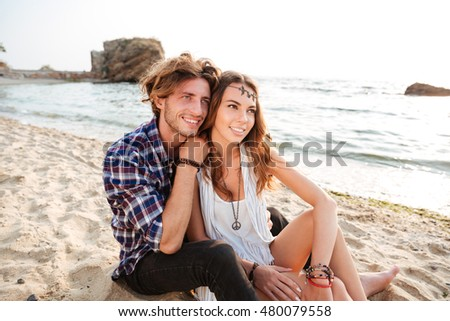 Happy young couple sitting and hugging on the beach #480079558