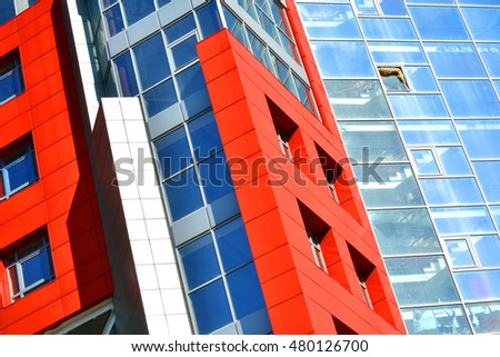 Part of the facade of a modern building with red walls, square windows, the blue mirrored glass. Architecture in a modern style and high-tech on bright sunny day. Building is photographed at an angle #480126700