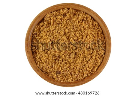 Top view of unrefined unbleached natural Brown sugar in brown color in a wooden bowl isolated on white background