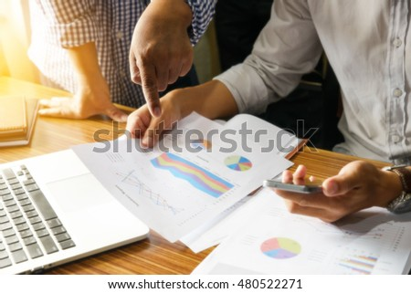 Boss pointed a finger at the paper,annual report,young business man holding a smart phone,notebook on wood table. #480522271