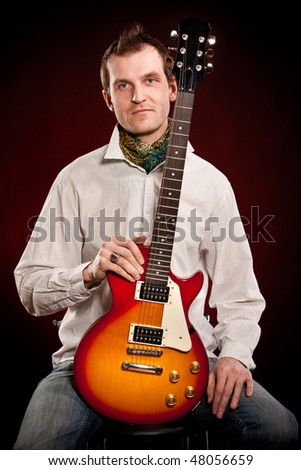 man with a guitar on a dark red background #48056659