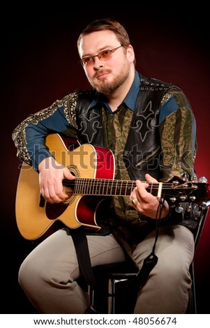 man with a guitar on a dark red background #48056674
