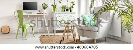Cozy and bright living room with work area and comfortable armchair #480604705