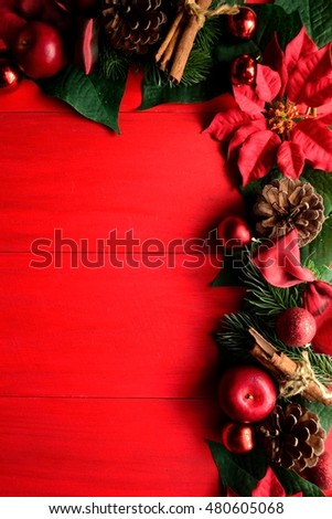 Red poinsettia with Christmas ornaments on red wooden background #480605068