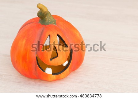 Orange pumpkin lantern with a spooky face smiling on a wooden grey background #480834778
