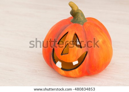 Orange pumpkin lantern with a spooky face smiling on a wooden grey background #480834853