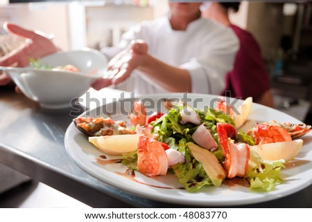 Seafood salad with stuffed mussel and prawns on commercial kitchen #48083770