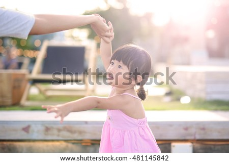 Portrait of girl with natural emotion smiling in the public garden at seaside #481145842
